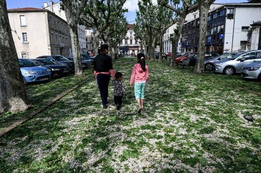 People walk on plane tree leaves fallen on a street of Romans-sur-Isere, southeastern France on June, 16, 2019, after a storm that caused one death in Haute-Savoie department and heavy damages in Drome department. (Photo by PHILIPPE DESMAZES / AFP)