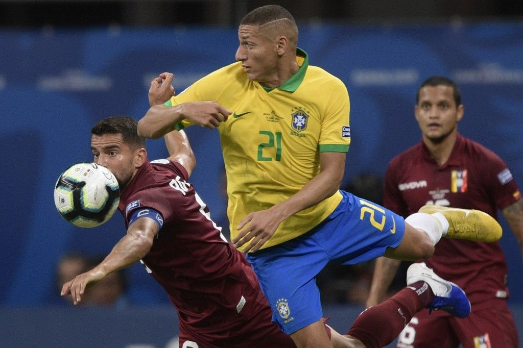 Venezuela's Tomas Rincon (L) and Brazil's Richarlison (C) vie for the ball during their Copa America football tournament group match at the Fonte Nova Arena in Salvador, Brazil, on June 18, 2019. (Photo by Juan MABROMATA / AFP)