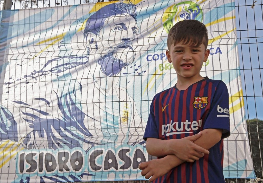 Brazilian six-year-old Lionel Messi Maier poses in front of a banner depicting Argentine football star Lionel Messi in Porto Alegre, Brazil, on June 21, 2019. - The child was named after the footballer, who will play against Qatar in Porto Alegre for a Copa America football match on June 23. (Photo by CARL DE SOUZA / AFP)