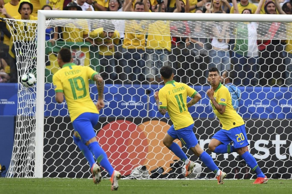 Brazil's Roberto Firmino (R) celebrates after scoring the team's second goal against Peru during their Copa America football tournament group match at the Corinthians Arena in Sao Paulo, Brazil, on June 22, 2019. (Photo by Nelson ALMEIDA / AFP)