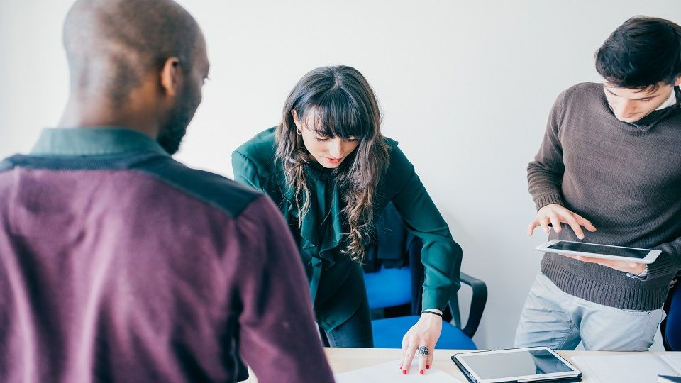 Group of contemporary multiethnic business people working together using tablet, talking to each other planning - working, business, start up concept