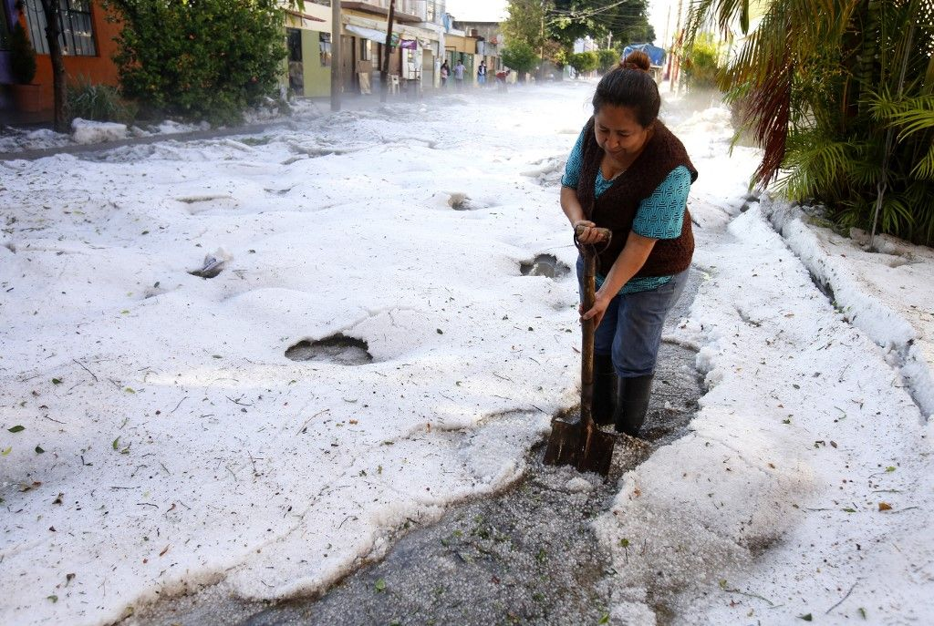 A woman tries to clear a street of Guadalajara, Jalisco State, Mexico, on June 30, 2019 after a hail storm fell in the area. - A freak hail storm on Sunday struck Guadalajara, one of Mexico's most populous cities, shocking residents and trapping vehicles in a deluge of ice pellets up to two metres deep. (Photo by Ulises RUIZ / AFP)