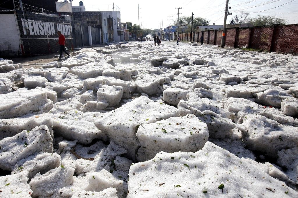 Picture of a street of Guadalajara, Jalisco State, Mexico, taken on June 30, 2019 after a hail storm fell in the area. - A freak hail storm on Sunday struck Guadalajara, one of Mexico's most populous cities, shocking residents and trapping vehicles in a deluge of ice pellets up to two metres deep. (Photo by Ulises RUIZ / AFP)