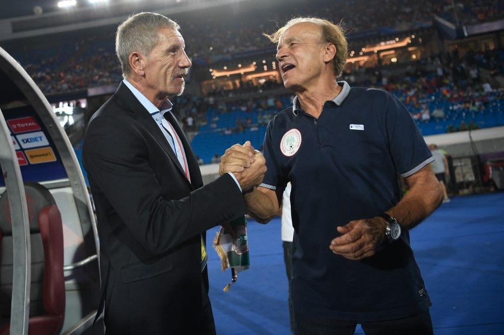 South Africa's coach Stuart Baxter (L) greets Nigeria's coach Gernot Rohr during the 2019 Africa Cup of Nations (CAN) quarter final football match between Nigeria and South Africa at Cairo international stadium on July 9, 2019. (Photo by Khaled DESOUKI / AFP)