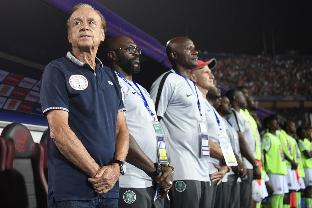 Nigeria's coach Gernot Rohr (L) and his bench stand for the national anthem during the 2019 Africa Cup of Nations (CAN) quarter final football match between Nigeria and South Africa at Cairo international stadium on July 9, 2019. (Photo by Khaled DESOUKI / AFP)