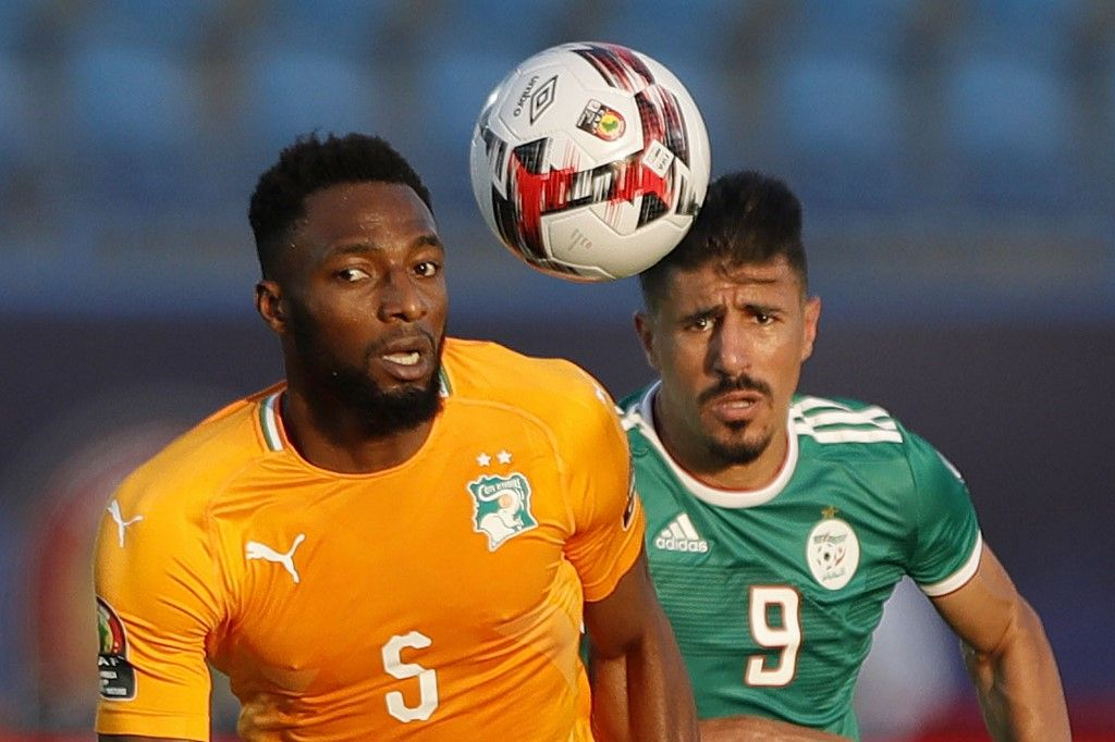 Ivory Coast's defender Wilfried Kanon (L) fights for the ball with Algeria's forward Baghdad Bounedjah during the 2019 Africa Cup of Nations (CAN) quarter final football match between Ivory Coast and Algeria at the Suez stadium in Suez on July 11, 2019. (Photo by FADEL SENNA / AFP)