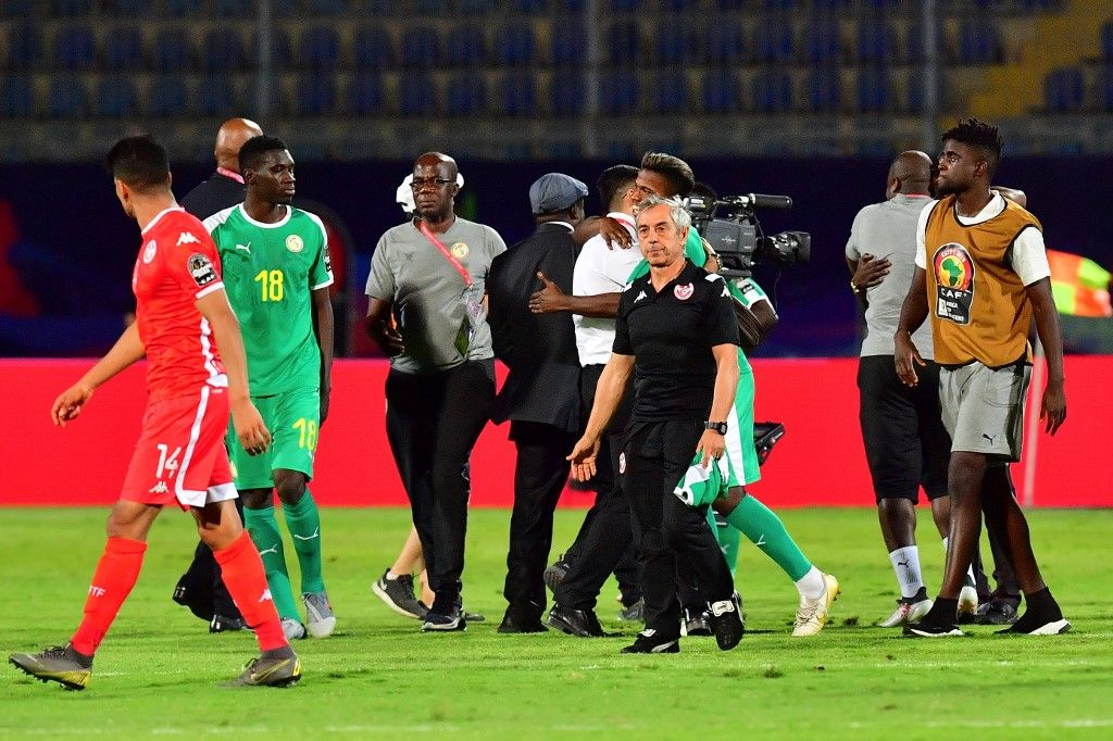 Senegalese players and staff celebrate next to Tunisia's coach Alain Giresse after winning the 2019 Africa Cup of Nations (CAN) Semi-final football match between Senegal and Tunisia at the 30 June stadium in Cairo on July 14, 2019. (Photo by Giuseppe CACACE / AFP)