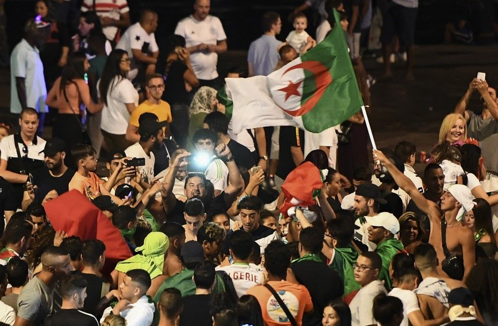 Algeria supporters celebrate after Algeria won the 2019 Africa Cup of Nations (CAN) semi-final football match against Nigeria, at the old harbour (vieux port) in Marseille, southern France, on July 14, 2019. - Riyad Mahrez rifled in a stoppage-time free-kick to earn Algeria a dramatic 2-1 victory over three-time champions Nigeria on July 14 and set up a rematch with Senegal in the Africa Cup of Nations final. (Photo by Boris HORVAT / AFP)