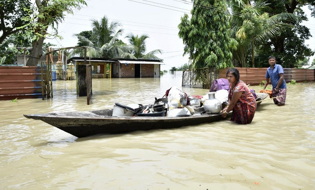 In this picture taken on July 16, 2019, an indian family shift belongings from their submerged house at the flood affected area of Hatishila in Kamrup district of Assam state. - Survivors scrambled for higher ground as torrential monsoon rains swept away homes and triggered landslides across South Asia on July 16, with millions of people affected and at least 180 dead, officials said. (Photo by Biju BORO / AFP)
