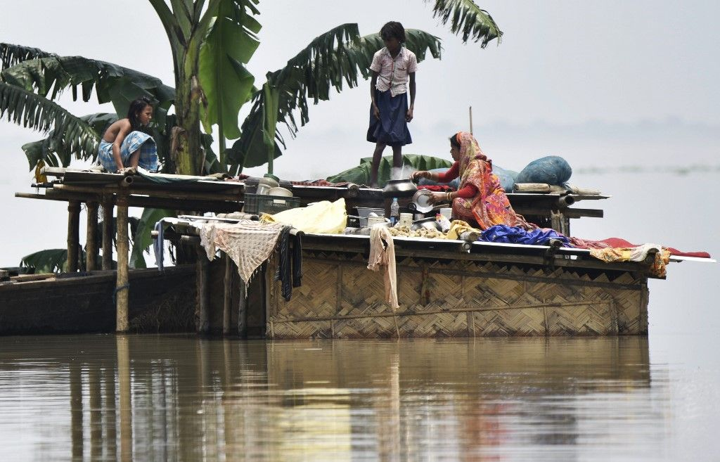 Members of an Indian family stand atop a hut at the flood affected area of Hatishila in Kamrup district of India's Assam state on July 16, 2019. - Survivors scrambled for higher ground as torrential monsoon rains swept away homes and triggered landslides across South Asia on July 16, with millions of people affected and at least 180 dead, officials said. (Photo by Biju BORO / AFP)