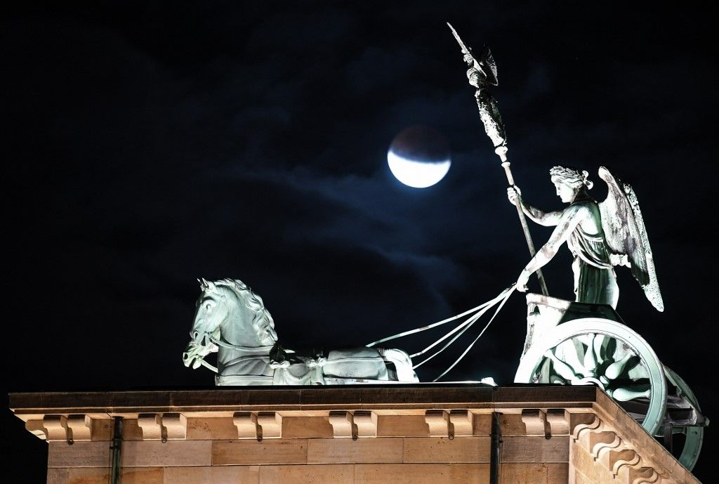 The moon is seen above the quadriga atop the Brandenburg Gate, Berlin's landmark, during a partial lunar eclipse on July 16, 2019. (Photo by Britta Pedersen / dpa / AFP) / Germany OUT