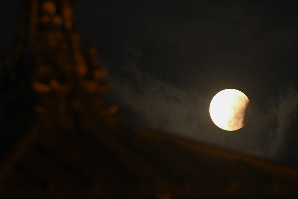 The moon is seen past the roof of a Hindu temple at Basantapur Durbar square during a partial lunar eclipse in Kathmandu on July 17, 2019. (Photo by PRAKASH MATHEMA / AFP)