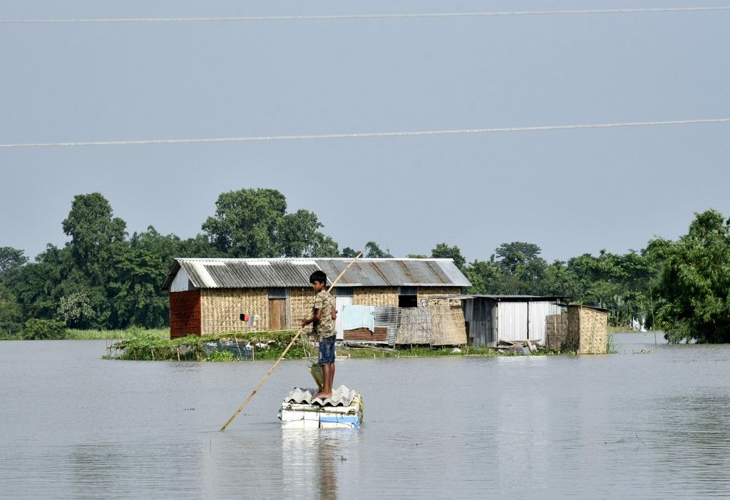 In this picture taken on July 16, 2019, an Indian boy paddles a raft near a submerged house, at the flood affected area of Kayakuchi village, in Barpeta district of Assam. - Survivors scrambled for higher ground as torrential monsoon rains swept away homes and triggered landslides across South Asia on July 16, with millions of people affected and at least 180 dead, officials said. (Photo by David TALUKDAR / AFP)