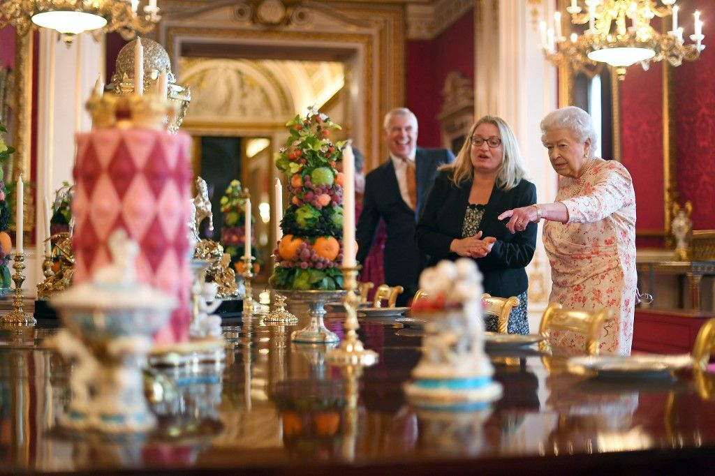 Britain's Queen Elizabeth II looks at a recreation of the 'Victoria' pattern dessert service in the State Dining Room, as part of an exhibition to mark the 200th anniversary of the birth of Queen Victoria, for the Summer Opening of Buckingham Palace in London on July 17, 2019. (Photo by Victoria Jones / POOL / AFP)