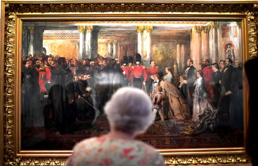 Britain's Queen Elizabeth II looks at a painting of Queen Victoria inspecting wounded Coldstream Guardsmen, 1855, by John Gilbert, as part of an exhibition to mark the 200th anniversary of the birth of Queen Victoria, for the Summer Opening of Buckingham Palace in London on July 17, 2019. (Photo by Victoria Jones / POOL / AFP)