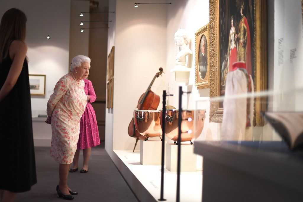 Britain's Queen Elizabeth II looks at musical instruments used by Queen Victoria's private orchestra, as part of an exhibition to mark the 200th anniversary of the birth of Queen Victoria, for the Summer Opening of Buckingham Palace in London on July 17, 2019. (Photo by Victoria Jones / POOL / AFP)