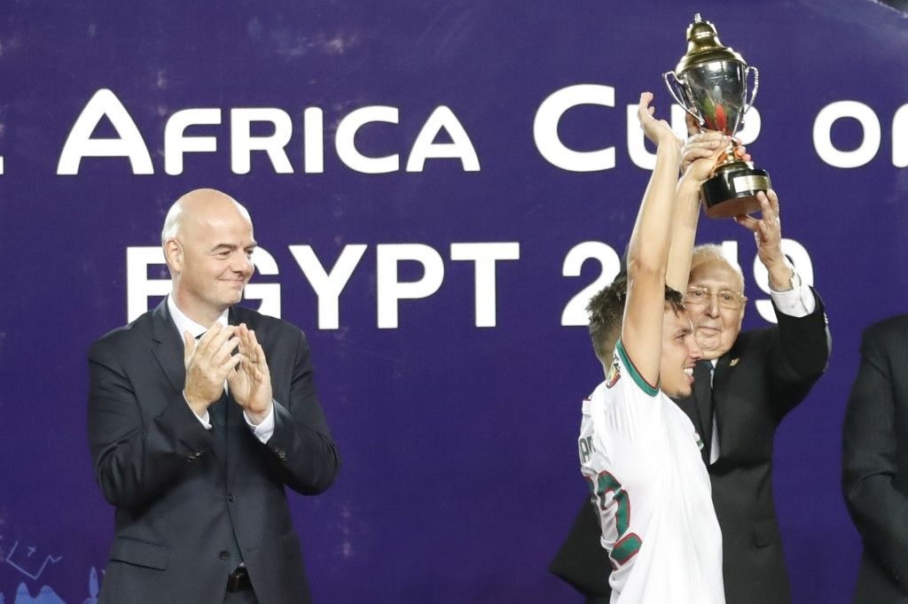 Algeria's interim president Abdelkader Bensalah (R) presents Algeria's midfielder Ismail Bennacer with the trophy of Best Young Player of the Tournament, next to FIFA President Gianni Infantino, during the 2019 Africa Cup of Nations (CAN) Final football match between Senegal and Algeria at the Cairo International Stadium in Cairo on July 19, 2019. (Photo by Khaled DESOUKI / AFP)