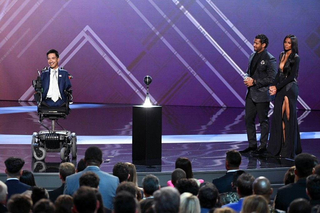 LOS ANGELES, CALIFORNIA - JULY 10: (L-R) Rob Mendez accepts the Jimmy V Award For Perseverance as Russell Wilson and Ciara listen onstage during The 2019 ESPYs at Microsoft Theater on July 10, 2019 in Los Angeles, California. Kevin Winter/Getty Images/AFP