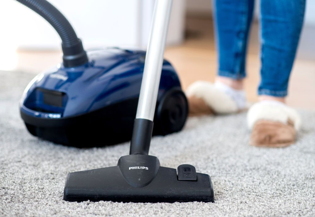 07 March 2019, Lower Saxony, Hannover: A woman in an apartment is vacuuming the floor with a Philips vacuum cleaner. Photo: Hauke-Christian Dittrich/dpa (Photo by Hauke-Christian Dittrich/picture alliance via Getty Images)