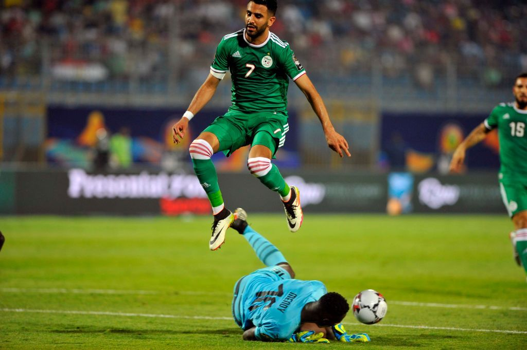 Algeria's Riyad Mahrez jumps over Senegal's goalkeeper Edouard Osoque Mendy during the African Cup of Nations group C soccer match between Algeria and Senegal at 30 June Stadium in Cairo, Egypt, Thursday, June 27, 2019. (Photo by Mohamed Mostafa/NurPhoto via Getty Images)