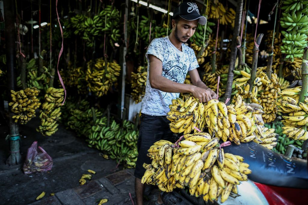 A man prepares bananas for sale at a traditional market in Jakarta, Indonesia, on July 7, 2019. (Photo by Andrew Gal/NurPhoto via Getty Images)