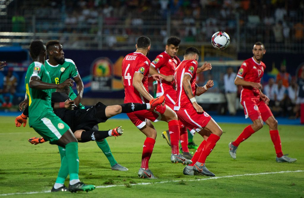 CAIRO, EGYPT - JULY 14: Goalkeeper Hassen Mouez of Tunisia dives to clear the ball but misses it as the ball hits Dylan Bronn, conceding an own goal during the 2019 Africa Cup of Nations Semi Final match between Senegal and Tunisia at 30th June Stadium on July 14, 2019 in Cairo, Egypt. (Photo by Visionhaus)