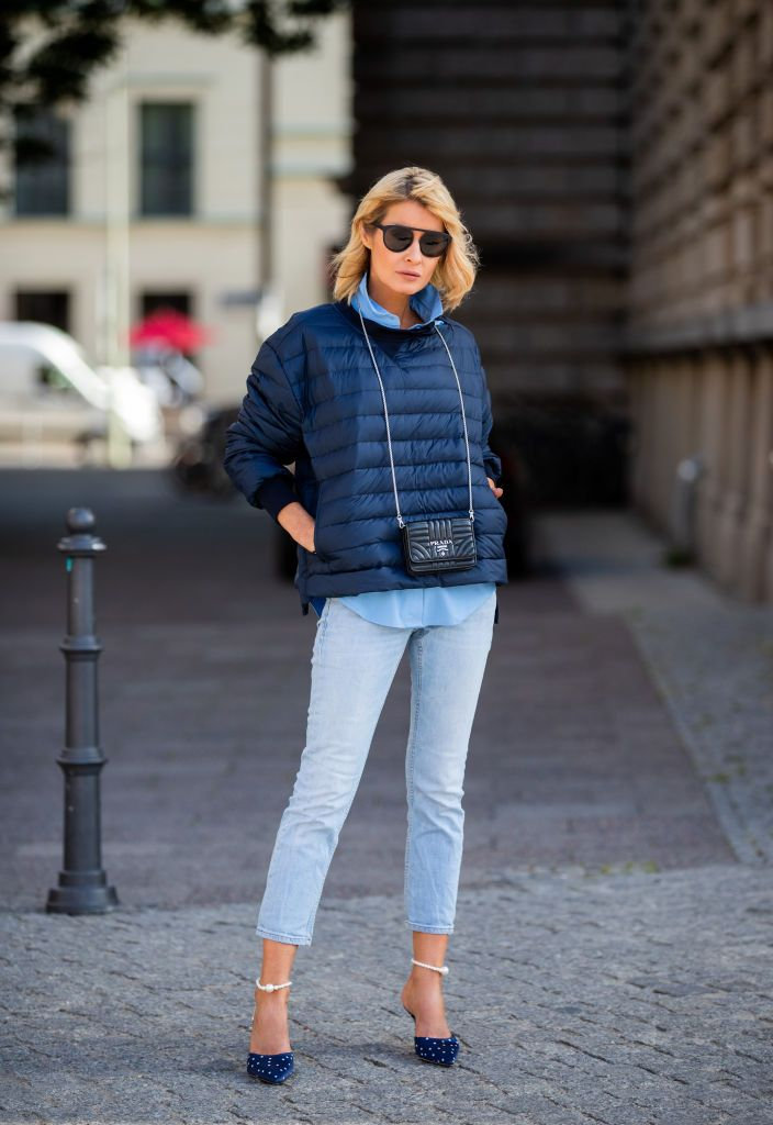 BERLIN, GERMANY - JULY 22: Gitta Banko is seen wearing a blue down sweater by Holubar, a blue blouse by Steffen Schraut, light blue jeans by Closed, navy and white polka dotted satin mules included ankle bracelets finished with pearlescent by Magda Butrym, black Prada micro bag and a black sunglasses by You Mawo on July 22, 2019 in Berlin, Germany. (Photo by Christian Vierig/Getty Images)