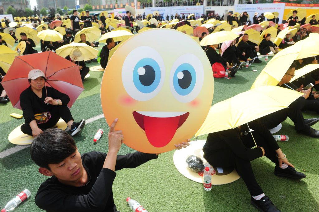 FUYANG, CHINA - MAY 27: People dress as emoji faces to set an Guinness World Record on a school playground on May 27, 2018 in Fuyang, Anhui Province of China. Guinness World Record of most people dressed up as emoji faces was achieved by 932 participants on Sunday in Fuyang. (Photo by VCG/VCG via Getty Images)