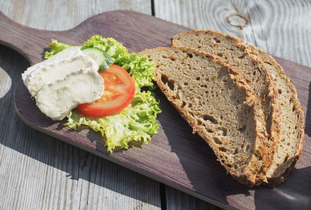 Bread produced using local ingredients from Upper Franconia on a plate with cheese and salad in Münchberg, Germany, 4 September 2017. Photo: Nicolas Armer/dpa (Photo by Nicolas Armer/picture alliance via Getty Images)