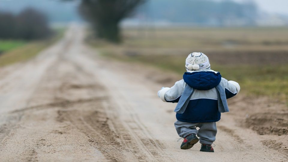 toddler child walking by rural sandy road in early springtime