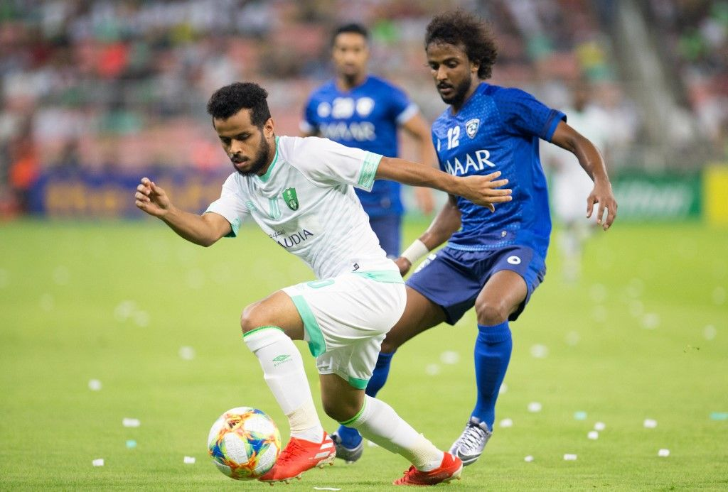 Ahli's forward Abdulfattah Asiri (L) is marked by Hilal's defender Yasser Shahrani during the AFC Champions League play-off football match between Saudi's al-Ahli and al-Hilal at King Abdullah Sports CIty Stadium in the city of Jeddah on August 6, 2019. (Photo by - / AFP)