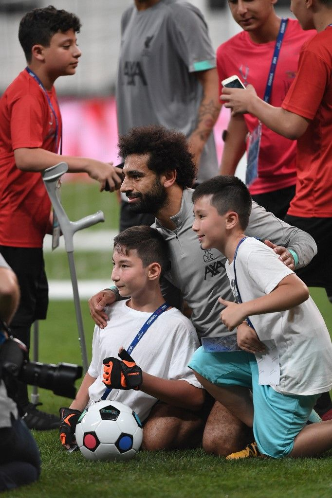 Liverpool's Egyptian midfielder Mohamed Salah (L) poses with children at the end of a training session ahead of the UEFA Super Cup 2019 football match between Liverpool and Chelsea at Besiktas Park stadium in Istanbul on August 13, 2019. (Photo by Ozan KOSE / AFP)