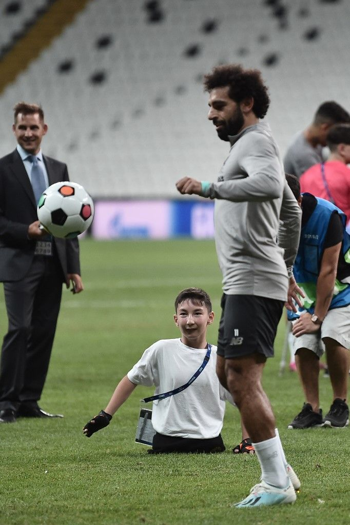 Liverpool's Egyptian midfielder Mohamed Salah (L) plays football with a child at the end of a training session ahead of the UEFA Super Cup 2019 football match between Liverpool and Chelsea at Besiktas Park stadium in Istanbul on August 13, 2019. (Photo by Ozan KOSE / AFP)