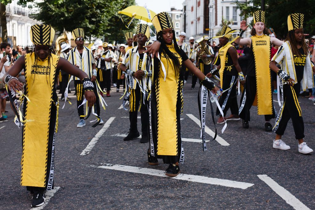 LONDON, UNITED KINGDOM - 2019/08/25: A dancing troupe performs at Westbourne Grove, during the opening day of the 2019 Notting Hill Carnival. Up to a million people are expected to pack the streets of Notting Hill and surrounding areas over the course of the two day event. The annual celebration of Afro-Caribbean culture takes place each August bank holiday weekend. (Photo by David Cliff/SOPA Images/LightRocket via Getty Images)