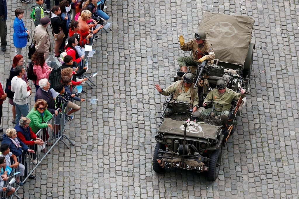 Participants in a military vehicle wave to the crowd as they take part in ceremonies marking the 75th anniversary of its World War Two liberation in Brussels, September 3, 2019.  REUTERS/Francois Lenoir