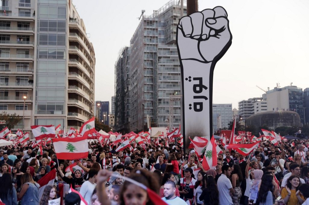 Lebanese demonstrators raise a large clenched fist with
