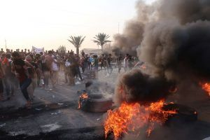 Demonstrators gather as they block the road with burning tires during a protest over unemployment, corruption and poor public services, in Baghdad, Iraq